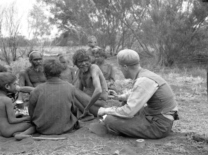 A history black and white photo of people sitting down in a group