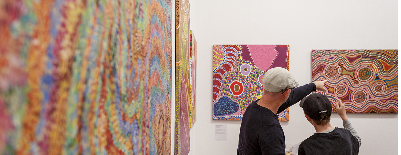 Father and son looking at Aboriginal paintings on an exhibition wall.