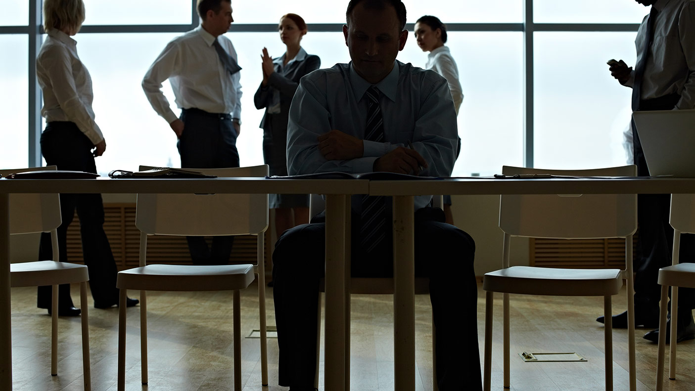 Male leader reading document table with business people cooperating with each other behind