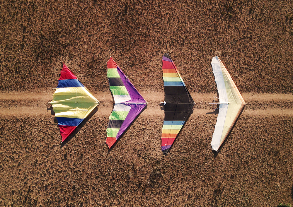 Four hang gliders on a sandy road