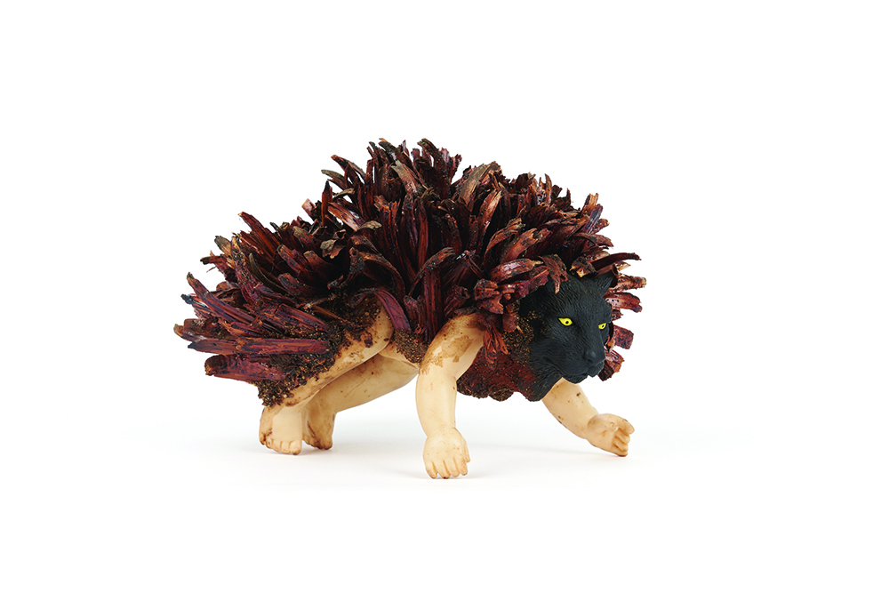 'GRRR', rubber doll body and animal head (both found on roadside, 1990s), Xanthorrhoea bracts, acrylic medium, 16 x 11 x 11 cm. On loan Anne M Brody Collection, Perth. Artist: Nalda Searles. Photographer Rebecca Mansell.
