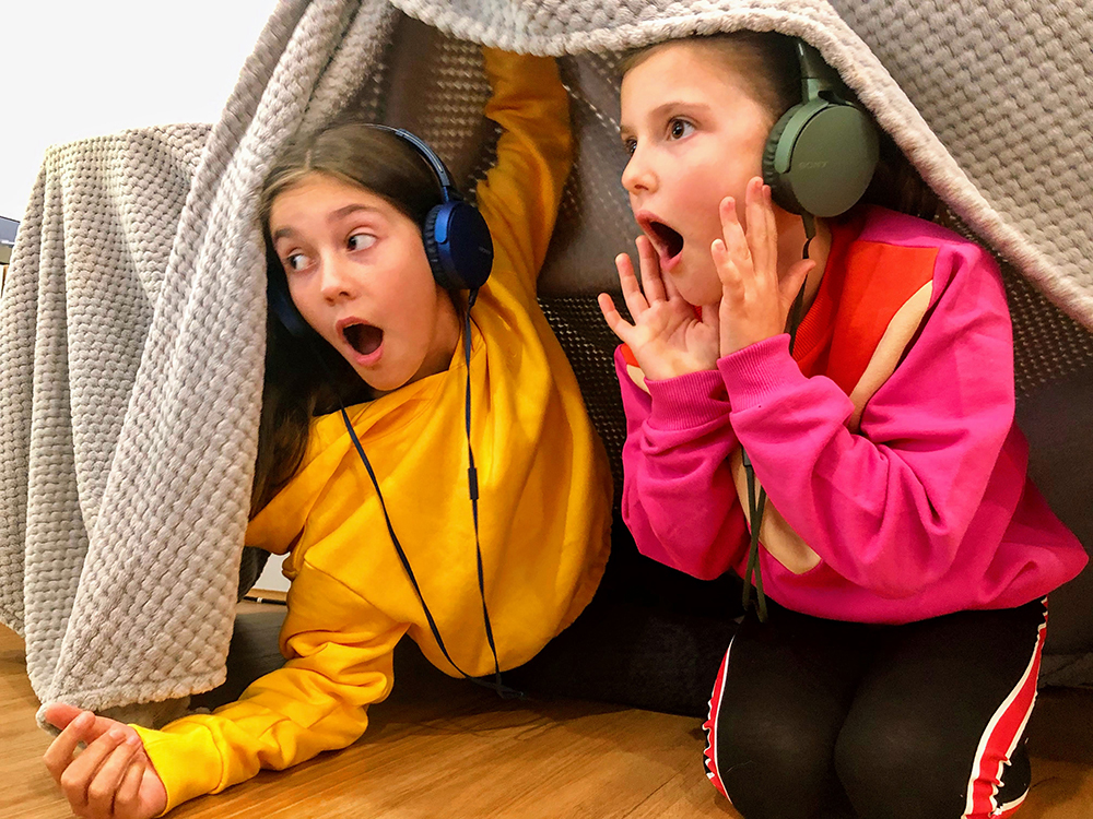 The Turners by Audioplay, 2020. Show two girls with headphones looking out of a inside cubby.