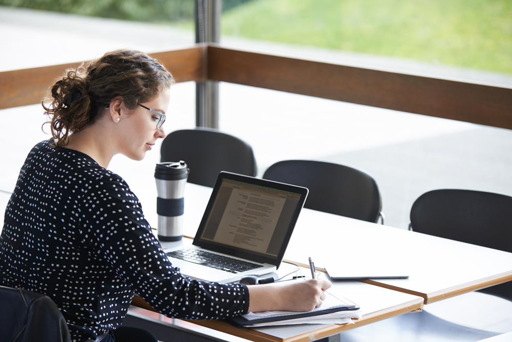 A woman woirking at a desk with a laptop and writing pad.