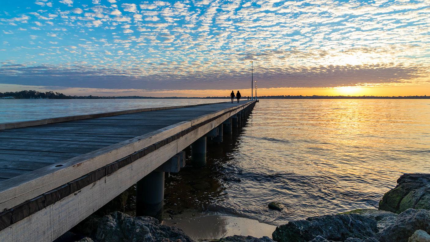 Pier over ocean against the sky during sunset - stock photo