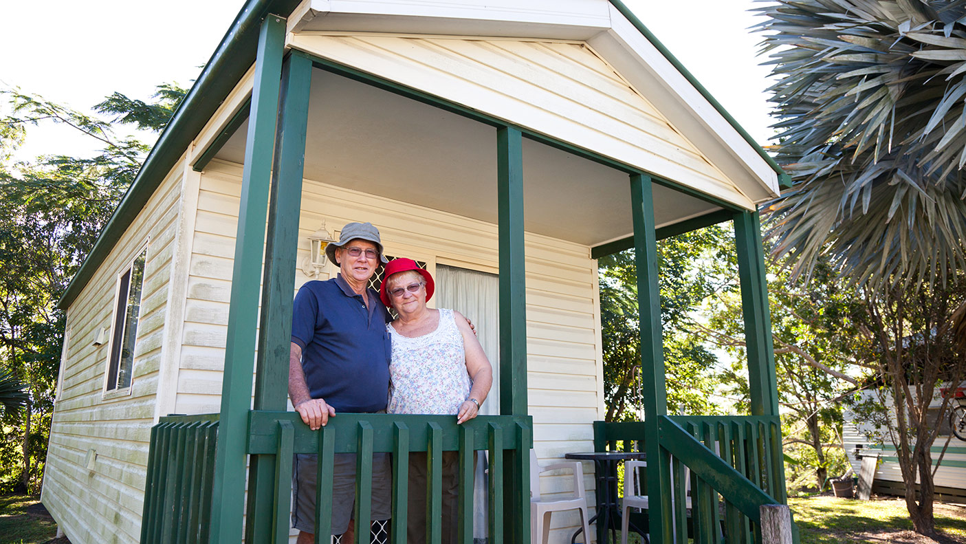 An elderly couple standing in front of their park home
