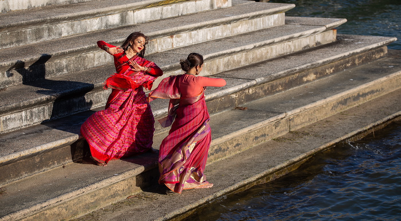 Two Indian female dancers dressed in traditional costumes dancing on the bank of a river.
