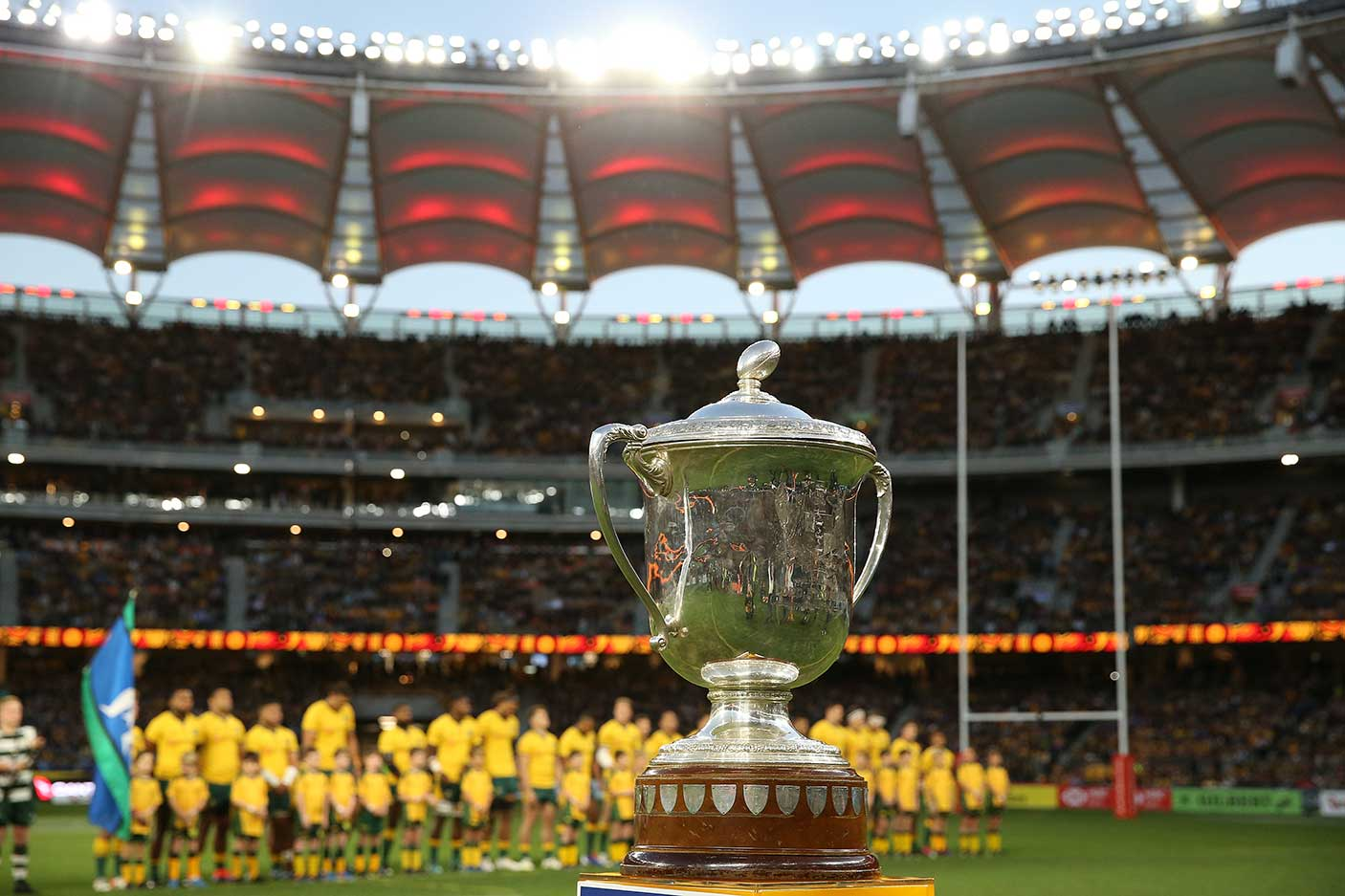 The Bledisloe Cup in focus with the Wallabies lined up behind it at Optus Stadium