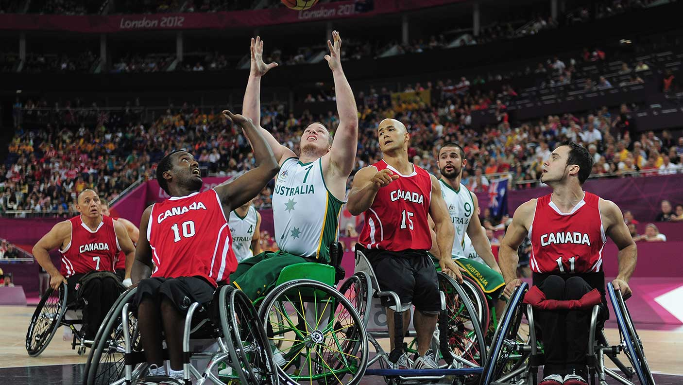 Shaun Norris of Australia is challenged by Abdi Dini and David Eng of Canada during the gold medal wheelchair basketball match between Australia and Canada