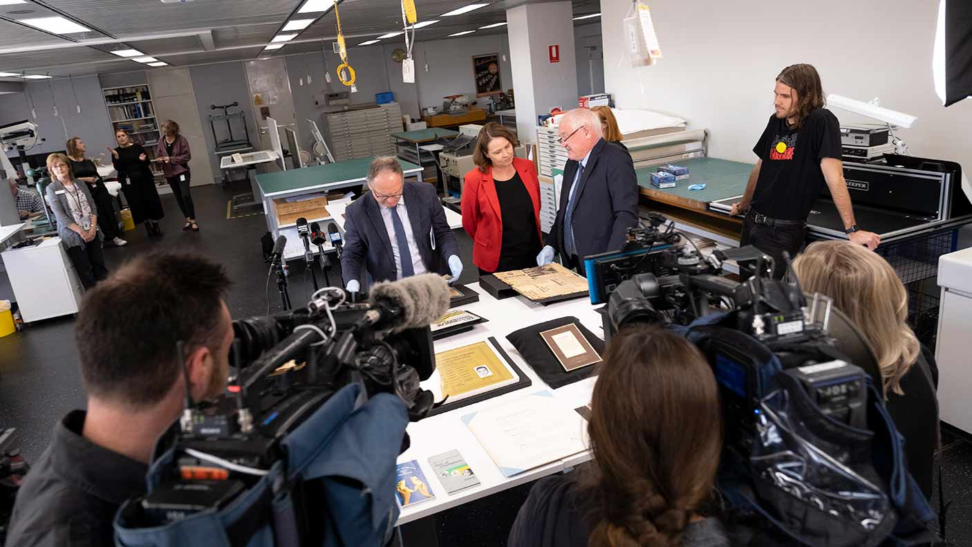 A group of people with media around desk with item from the collection