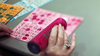 Closeup image of a bingo player marking off numbers