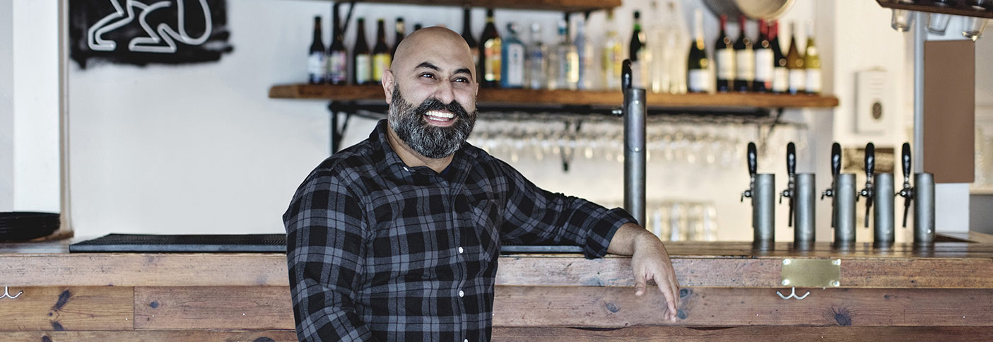 Stock image of a publican leaning on a bar