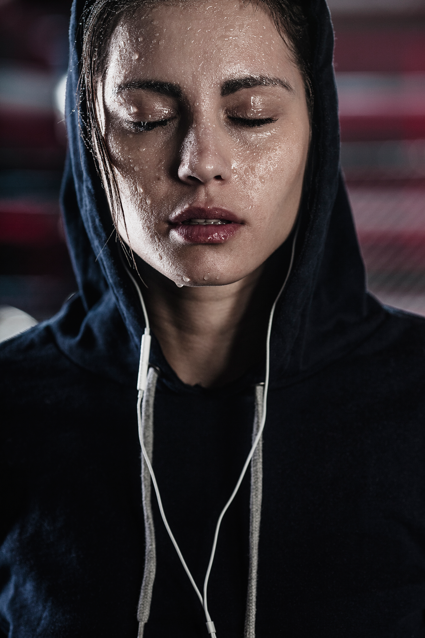 Woman in hooded shirt with sweat on face at gym - stock photo