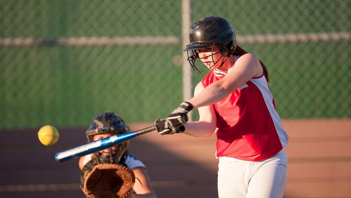 Softball player hits softball while batting