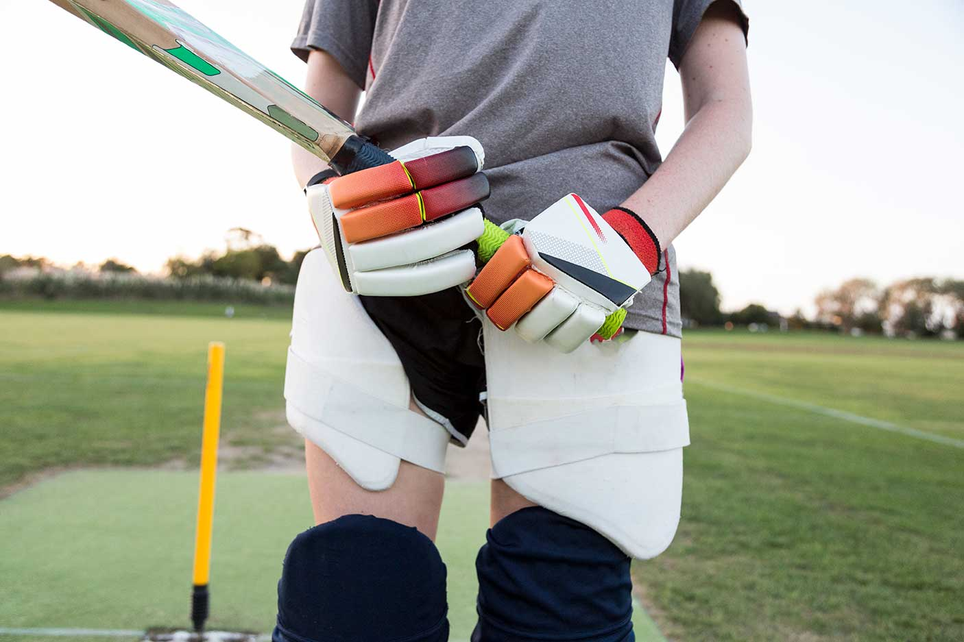 Close up of female cricketer wearing gloves and pads