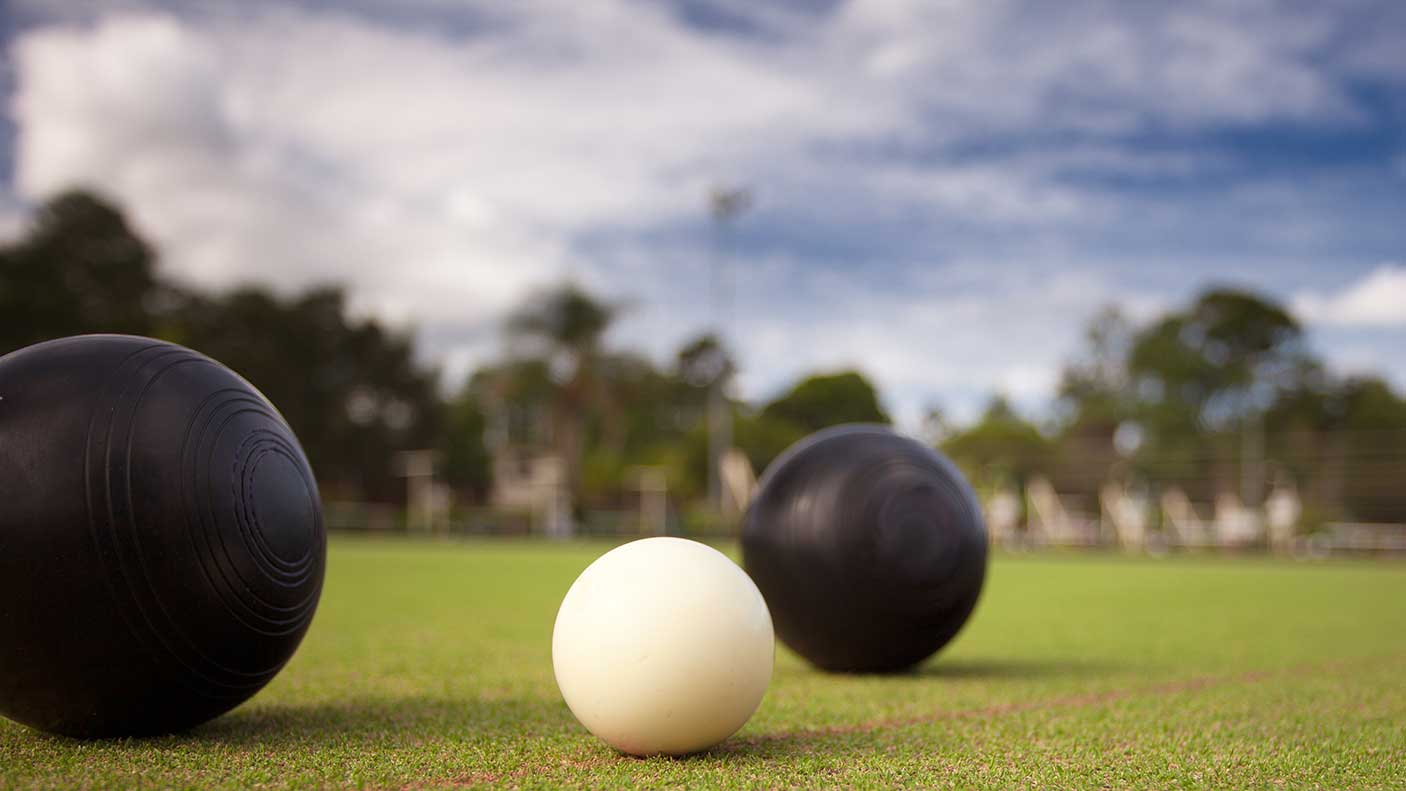 Lawn bowls with a close up photo of the bowl and jack, photographed close up low profile shot showing the green grass bowling surface in the background.