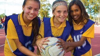 Three junior netballers holding a netbal