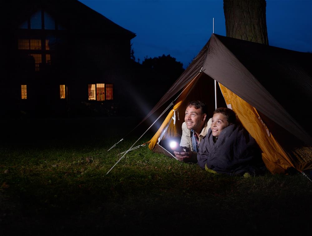 Father and child camping in backyard