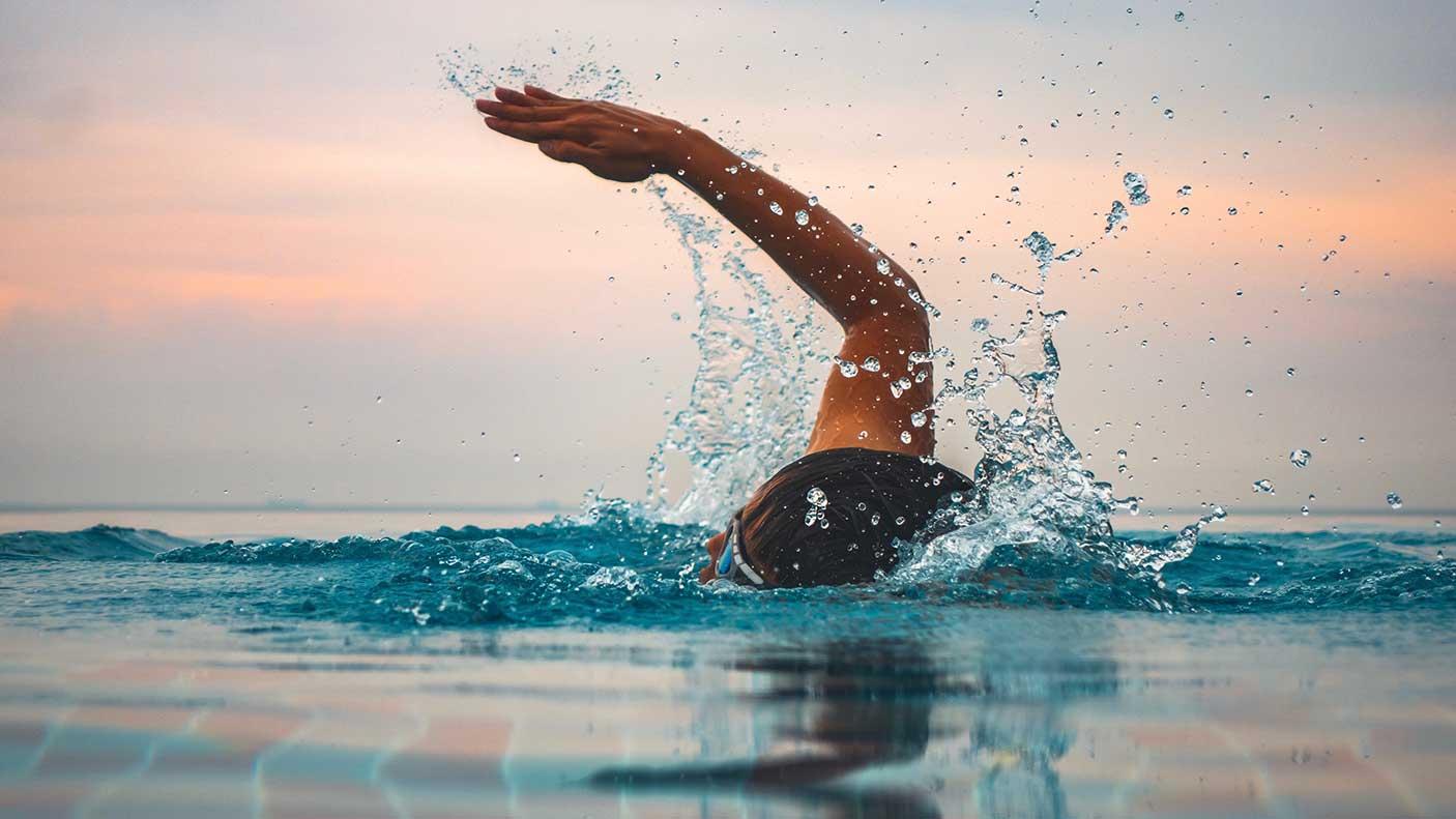 Swimmer against sky during sunset