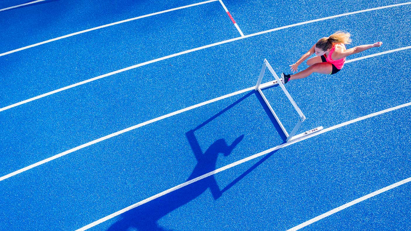 Top view of female runner crossing hurdle on tartan track